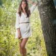 Attractive young woman in white short dress posing near a tree in a sunny summer day. Beautiful girl enjoying the nature in a green forest. Portrait of sensual female in white daydreaming in a meadow — Stock Photo #61217917