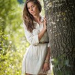 Attractive young woman in white short dress posing near a tree in a sunny summer day. Beautiful girl enjoying the nature in a green forest. Portrait of sensual female in white daydreaming in a meadow — Stock Photo #61217939