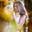 Young beautiful girl in a yellow dress in the woods. Portrait of romantic woman in fairy forest. Stunning fashionable teenage model in autumnal meadow, outdoor shot. Cute brunette long hair female. — Stock Photo #61233485
