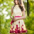 Young beautiful girl in a yellow dress in the woods. Portrait of romantic woman in fairy forest. Stunning fashionable teenage model in summer meadow, outdoor shot. Cute brunette long hair female. — Stock Photo #61237269