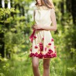Young beautiful girl in a yellow dress in the woods. Portrait of romantic woman in fairy forest. Stunning fashionable teenage model in summer meadow, outdoor shot. Cute brunette long hair female. — Stock Photo #61237275