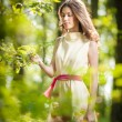 Young beautiful girl in a yellow dress in the woods. Portrait of romantic woman in fairy forest. Stunning fashionable teenage model in summer meadow, outdoor shot. Cute brunette long hair female. — Stock Photo #61237283