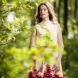 Young beautiful girl in a yellow dress in the woods. Portrait of romantic woman in fairy forest. Stunning fashionable teenage model in summer meadow, outdoor shot. Cute brunette long hair female. — Stock Photo #61237287