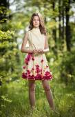 Young beautiful girl in a yellow dress in the woods. Portrait of romantic woman in fairy forest. Stunning fashionable teenage model in summer meadow, outdoor shot. Cute brunette long hair female. — Stock Photo