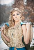 Lovely young lady in elegant dress posing winter scenery, royal look. Fashionable blonde woman with forest in background, outdoor shoot. Glamorous female with long fair hair in nature - princess style — Stock Photo