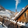 Old wooden cottage with hill covered by snow in background. Bright cold winter day in the mountains landscape. Carpathian mountains, Romania. Isolated wood mountain house cabin hut covered by snow — ストック写真 #61481909