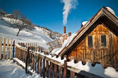 Old wooden cottage with hill covered by snow in background. Bright cold winter day in the mountains landscape. Carpathian mountains, Romania. Isolated wood mountain house cabin hut covered by snow — Foto Stock