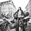 Attractive young woman in urban fashion shot near motorcycle. Beautiful fashionable young girl in black leather outfit holding a helmet posing in front of high speed motorbike, black and white photo — Stock Photo #61506491