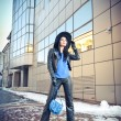 Attractive young woman in a winter fashion shot. Beautiful fashionable young girl in black leather with big hat and blue handbag posing in front of modern building, urban scenery. — Stock Photo #61506495