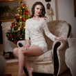 Beautiful sexy woman with Xmas tree in background sitting on elegant chair in cozy scenery. Portrait of girl posing pretty with short dress and bare feet. Attractive brunette female, indoor shot. — Stock Photo #61589453