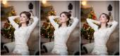 Beautiful sexy woman with Xmas tree in background sitting on elegant chair in cozy scenery. Portrait of girl posing pretty with short tight fit white dress. Attractive brunette female, indoor shot. — Stock Photo