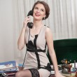 Happy smiling attractive woman wearing an elegant dress and black stockings talking by phone in an office scenery. Beautiful young sensual female with short dress sitting on desk holding the phone — Stock Photo #61803255