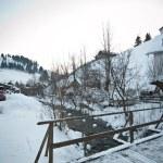 Wooden bridge in a traditional Romanian village across a small river. Bridge over frozen river. Winter landscape countryside, Moeciu, Romania. Wooden bridge over small frozen brook covered with snow — Stock Photo #61919813