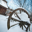 Old wooden cottage and wooden Romanian wheel covered by snow. Cold winter day at countryside. Traditional Carpathian mountains village scenery, Romania. Small cabin covered by snow — Stock Photo #61919815