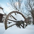 Old wooden cottage and wooden Romanian wheel covered by snow. Cold winter day at countryside. Traditional Carpathian mountains village scenery, Romania. Small cabin covered by snow — Stock Photo #61919817