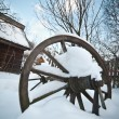 Old wooden cottage and wooden Romanian wheel covered by snow. Cold winter day at countryside. Traditional Carpathian mountains village scenery, Romania. Small cabin covered by snow — Stock Photo #61919819