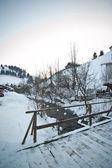 Wooden bridge in a traditional Romanian village across a small river. Bridge over frozen river. Winter landscape countryside, Moeciu, Romania. Wooden bridge over small frozen brook covered with snow — Stockfoto