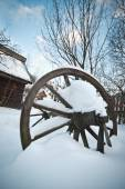 Old wooden cottage and wooden Romanian wheel covered by snow. Cold winter day at countryside. Traditional Carpathian mountains village scenery, Romania. Small cabin covered by snow — Stock fotografie