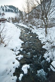 View of frozen river countryside. Brook in snowy landscape. Romanian small river in winter scenery, Romania, Moeciu. Wild brook in winter season. — Stock fotografie