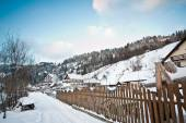 Narrow road covered by snow at countryside. Winter landscape with snowed trees, road and wooden fence. Cold winter day at countryside. Traditional Carpathian mountains village scenery, Romania — Stock Photo