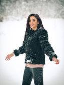 View of happy brunette girl playing with snow in winter landscape. Beautiful young female on winter background. Attractive young woman in warm soft clothes outdoor in a winter day — Stock Photo