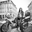 Attractive young woman in urban fashion shot near motorcycle. Beautiful fashionable young girl in black leather outfit holding a helmet posing in front of high speed motorbike, black and white photo — Stock Photo #63208645