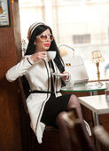 Fashionable young woman in black and white outfit drinking coffee in restaurant. Beautiful brunette in elegant scenery holding a cup of coffee. Attractive lady with sunglasses and coat in coffee shop — Stockfoto