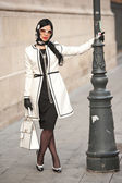 Attractive young woman in winter fashion shot. Beautiful fashionable young girl in black and white outfit posing on avenue. Elegant brunette with headscarf, sunglasses and handbag in urban scenery. — Stock Photo