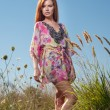 Beautiful young woman in wild flowers field on blue sky background. Portrait of attractive red hair girl with long hair relaxing in nature, outdoor shot. Lady in multicolored dress enjoying nature — Stock Photo #64456223