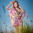 Beautiful young woman in wild flowers field on blue sky background. Portrait of attractive red hair girl with long hair relaxing in nature, outdoor shot. Lady in multicolored dress enjoying nature — Stock Photo #64456283