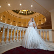 Young beautiful luxurious woman in wedding dress posing in luxurious interior. Bride with huge wedding dress in majestic manor. Seductive blonde bride with gorgeous gown and long dally posing — Stock Photo #64699135