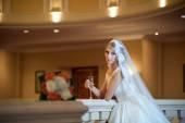 豪華なインテリアでポーズがウェディング ドレスで若い美しい豪華な女性。雄大なマナーで巨大なウェディング ドレスと花嫁。豪華なガウンと長い魅惑的な金髪の花嫁ダリー ポーズ — ストック写真