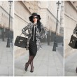 Attractive young woman in a winter fashion shot. Beautiful fashionable young girl in black posing on avenue. Elegant brunette with hat, sunglasses and handbag in urban scenery. — Stock Photo #66997381