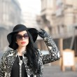 Attractive young woman in a winter fashion shot. Beautiful fashionable young girl in black posing on avenue. Elegant brunette with hat, sunglasses and gloves in urban scenery. — Stock Photo #66997383
