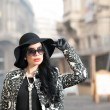 Attractive young woman in a winter fashion shot. Beautiful fashionable young girl in black posing on avenue. Elegant brunette with hat, sunglasses and gloves in urban scenery. — Stock Photo #66997395