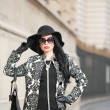 Attractive young woman in a winter fashion shot. Beautiful fashionable young girl in black posing on avenue. Elegant brunette with hat, sunglasses and handbag in urban scenery. — Stock Photo #66997419