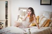 Young beautiful sexy woman in white short tight dress posing challenging indoor on vintage bed. Sensual long hair brunette in bedroom. Attractive female lying provocatively on bed full of pillows — Stock Photo