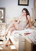 Young beautiful sexy woman in white short tight dress posing challenging indoor on vintage bed. Sensual long hair brunette on high heels in bedroom. Attractive female sitting provocatively on bed — Stock Photo