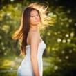 Beautiful young woman posing in a summer meadow. Portrait of attractive brunette girl with long hair relaxing in nature, outdoor shot in sunny day. Lady in white enjoying the nature, harmony concept — Stock Photo #69540625