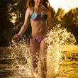 Sexy brunette woman in swimsuit running in river water. Sexy young woman playing with water during sunset. Beautiful woman wearing bikini enjoying the water  in the evening, frontal view — Stock Photo #69540639