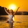 Sexy brunette woman in wet white lingerie posing in river water with sunset on background. Young female at the beach in twilight scenery. Attractive girl in summer evening over dramatic sky. — Stock Photo #69540671