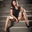 Fashionable pretty young woman with long legs sitting on old stone stairs. Beautiful long hair brunette on high heels shoes posing provocatively. Young model wearing black short dress, frontal view — Stock Photo #69540715