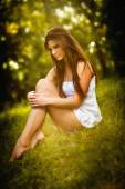 Attractive young woman in white short dress sitting on grass in a sunny summer day. Beautiful girl enjoying the nature in a green forest. Portrait of sensual female in white daydreaming in a meadow — Stock Photo