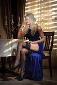 Mulher loira atraente elegante vestido longo sentado perto de uma mesa em um luxuoso interior clássico. lindo modelo loiro mostrando suas pernas longas em meias pretas. senhora sensual em um cenário vintage — Fotografia Stock