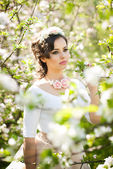 Portrait of beautiful girl posing outdoor with flowers of the cherry trees in blossom during a bright spring day. Attractive brunette woman with flowers accessories in orchard, spring shot — Stock Photo