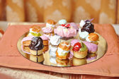 Wedding decoration with colored cupcakes, meringues and muffins. Elegant and luxurious event arrangement with colorful cakes. Wedding dessert. Set of tasty mini cakes on table — Stock Photo