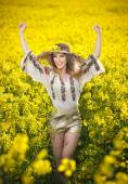 Young girl wearing Romanian traditional blouse posing in canola field with cloudy sky in background, outdoor shot. Portrait of beautiful blonde with straw hat smiling in rapeseed field — Stock Photo