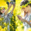 Woman wearing Romanian traditional blouse taking a selfie with a camera and checking her smart phone in canola field, outdoor shot. Portrait of beautiful blonde enjoying the yellow flowers of rapeseed — Stock Photo #74639813