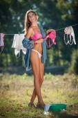 Sexy brunette woman in bikini and shirt putting clothes to dry in sun. Sensual young female with long legs putting out the washing to dry in sunny day. Perfect body housewife, outdoor shot in forest — Stock Photo