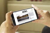 Smartphone with news publication on screen — Stock Photo